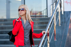 Woman in red jacket standing on the shop Stock Image