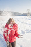 Woman in a red jacket. Throws snow royalty free stock photography