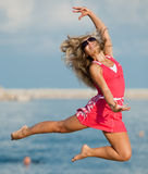 Woman in red is jumping. Attractive young woman in red dress jumping on the background of the sky Stock Image