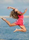Woman in red is jumping. Attractive young woman in red dress jumping on the background of the sky Stock Photo