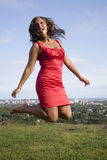 Woman in Red with Jumps. Letting out her inner child, she jumps in a hilltop meadow far from the city below stock image