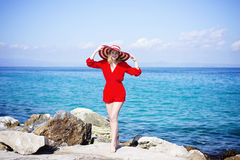 Woman in red jumpsuit and hat. In Greece Stock Photo