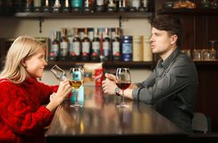 Woman in red knitted sweater tasting wine at bar counter. With young handsome sommelier, pleasant talk between girl and barman at workplace Stock Photography