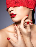 Woman with red lacy ribbon on eyes Stock Image