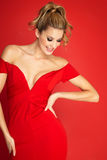 Woman On Red. Lady in red dress over red background Stock Photo