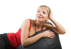 Woman in red laying on sofa. Young blond woman in red laying on black sofa, isolated on white Stock Photography