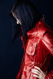 Woman in red leather jacket. Beautiful young woman with dark hair in structured bob wearing a red leather jacket on dark studio background royalty free stock photography