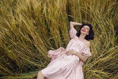 Woman in a red light dress lies in a field Stock Photo
