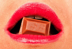 Woman with red lips biting a chocolate Stock Image