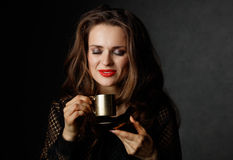 Woman with red lips enjoying cup of coffee on dark background Stock Photography