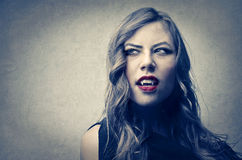 Vampire woman. Woman the red lips long brown hair and vampire teeth Stock Photo