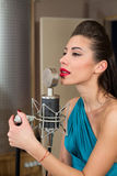 Woman with red lips sing in room with microphone Stock Photography