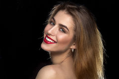 Woman with red lips smiling. Cheerful young woman with red lips looking at the camera and smiling in studio on black background Stock Images