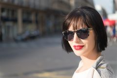 Woman with red lips in sunglasses walk on street. Woman or girl with red lips in sunglasses walk on street on sunny day. Fashion, beauty, look, style concept Royalty Free Stock Photo