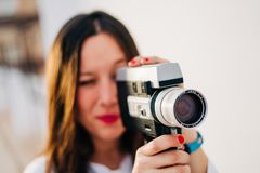 Woman with red lips using a retro video camera on a white background royalty free stock images