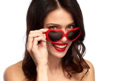 Woman with red lipstick and heart shaped shades. Valentines day, beauty and people concept - close up of happy smiling young woman with red lipstick and heart Stock Image
