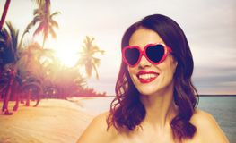 Woman with red lipstick and heart shaped shades. Valentines day, beauty and people concept - happy smiling young woman with red lipstick and heart shaped Stock Image