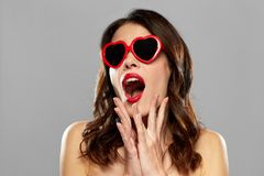 Woman with red lipstick and heart shaped shades. Valentines day, beauty and people concept - happy smiling young woman with red lipstick and heart shaped Royalty Free Stock Image