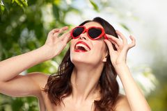 Woman with red lipstick and heart shaped shades. Valentines day, beauty and people concept - happy smiling young woman with red lipstick and heart shaped Stock Images