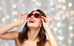 Woman with red lipstick and heart shaped shades. Valentines day, beauty and people concept - happy smiling young woman with red lipstick and heart shaped Royalty Free Stock Photography