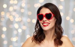 Woman with red lipstick and heart shaped shades. Valentines day, beauty and people concept - happy smiling young woman with red lipstick and heart shaped Royalty Free Stock Photo