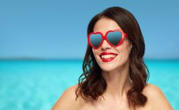 Woman with red lipstick and heart shaped shades. Valentines day, beauty and people concept - happy smiling young woman with red lipstick and heart shaped Royalty Free Stock Photos