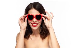 Woman with red lipstick and heart shaped shades. Valentines day, beauty and people concept - happy smiling young woman with red lipstick and heart shaped Stock Photography