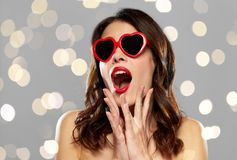 Woman with red lipstick and heart shaped shades. Valentines day, holidays, beauty and people concept - amazed young woman with red lipstick and heart shaped Stock Images