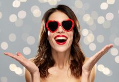 Woman with red lipstick and heart shaped shades. Valentines day, holidays, beauty and people concept - happy smiling young woman with red lipstick and heart Royalty Free Stock Photos