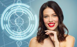 Woman with red lipstick over dna molecule. Beauty, genetics and people concept - happy smiling young woman with red lipstick posing over blue background and dna stock image