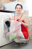 Woman in red loading the washing machine Stock Photo