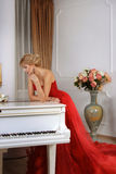 Woman in red long dress leaning over white piano Stock Photos