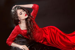 Woman in red lying in the dark. Fashion tempting girl model in s Royalty Free Stock Photography