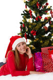 Woman in red lying under Christmas tree with gifts Stock Image