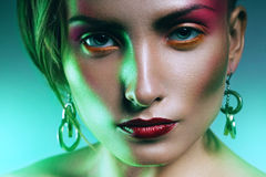Woman with red make up in green light Stock Images