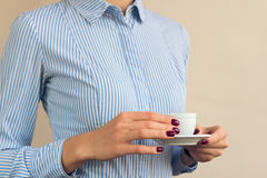 Woman with red manicure and blue shirt holding a Cup of coffee  Royalty Free Stock Photo