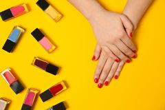 Woman with red manicure and nail polish bottles on color background. Top view stock photos