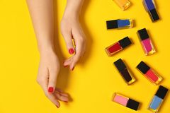 Woman with red manicure and nail polish bottles. On color background, top view stock photography