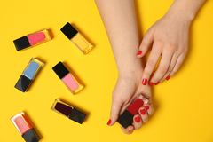 Woman with red manicure and nail polish bottles on color background. Top view stock photo