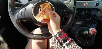 Woman in red mini dress on drivers seat in sport car holds in her hand Israeli money100 new shekels banknote stock images