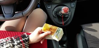 Woman in red mini dress in sport car holds in her hand Israeli money stack of new shekels stock image