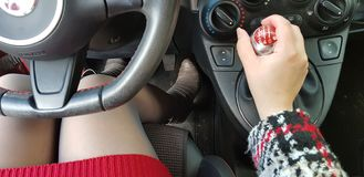 Woman in red mini dress and gray high heels boots sitting in mini sport car royalty free stock image