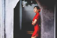 Woman in Red Mini Dress Leaning on Wall Stock Image