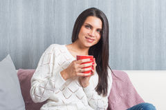 A woman  with a red mug in her hands, smiles sittings on the couch, sofa look at camera Stock Images