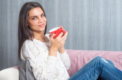 A woman  with a red mug in her hands, smiles sittings on the couch, sofa look at camera Stock Photography