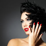 Woman with red nails and creative hairstyle. Beautiful fashion woman with red nails, creative hairstyle and makeup - Model posing in studio stock photos
