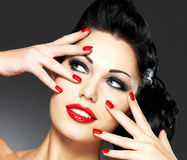 Woman with red nails and creative hairstyle. Beautiful fashion woman with red nails, creative hairstyle and makeup - Model posing in studio stock image