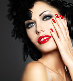 Woman with red nails and creative hairstyle. Beautiful fashion woman with red nails, creative hairstyle and makeup - Model posing in studio royalty free stock photography