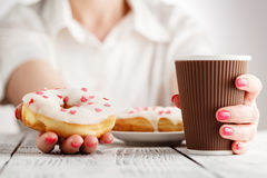 Woman with red nails sitting and holding a donut and hot cup of coffee Stock Images