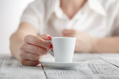 Woman with red nails sitting and holding a hot cup of coffee Royalty Free Stock Images